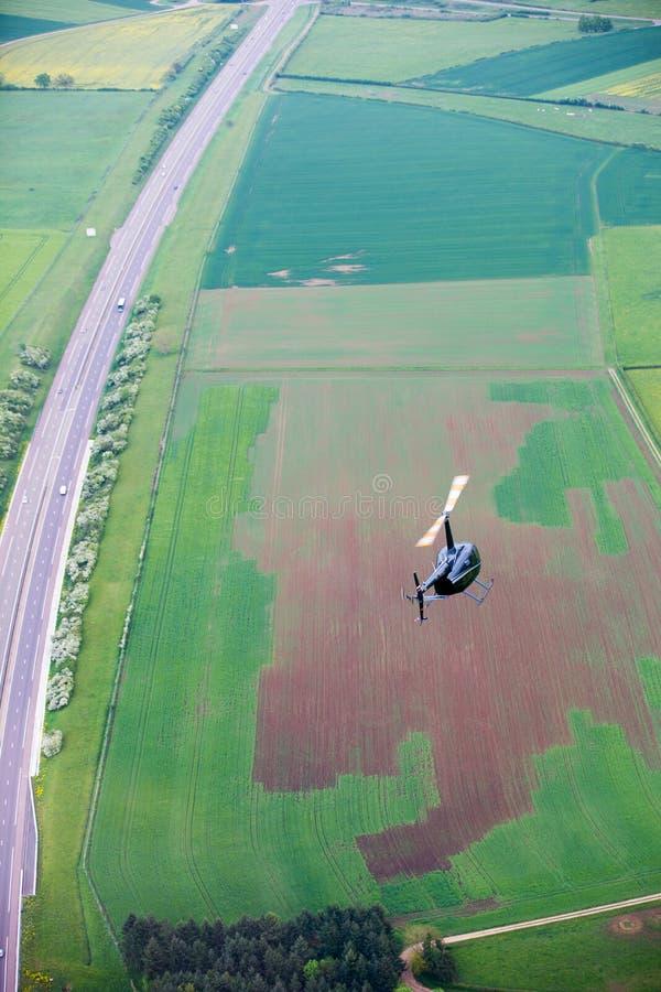 Kleiner grüner Hubschrauber über landwirtschaftlichen Feldern lizenzfreie stockfotografie