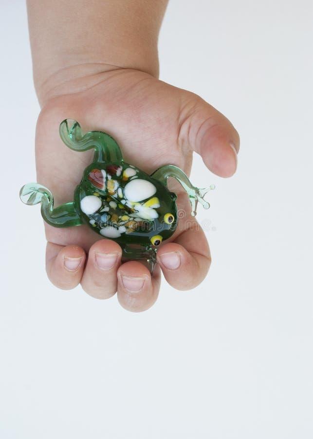 Kleiner gr?ner Frosch gemacht vom Glas in den H?nden eines Kindes auf einem wei?en Hintergrund stockfotos