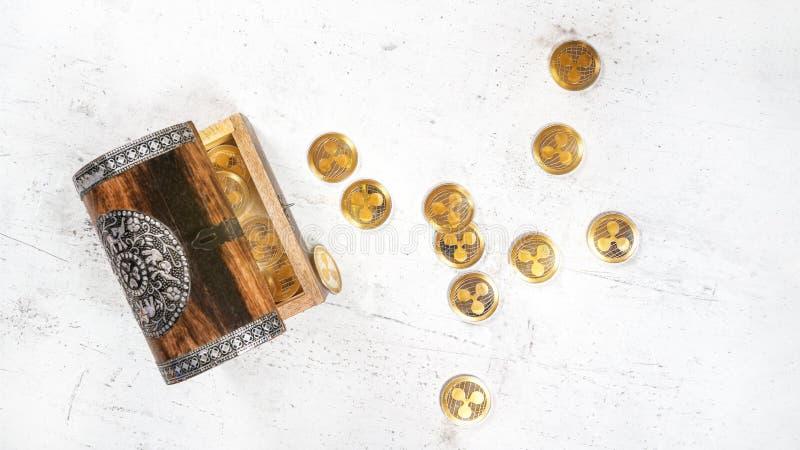 Kleiner hölzerner verzierter Kasten mit XRP-Kräuselung cryptocurrency goldenen Münzen, einige zerstreut auf weißes Steinbrett stockbild