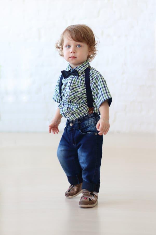Kleiner hübscher gelockter Junge in den Jeans stockbilder