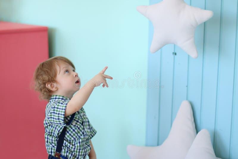 Kleiner hübscher gelockter Junge schaut oben lizenzfreies stockfoto