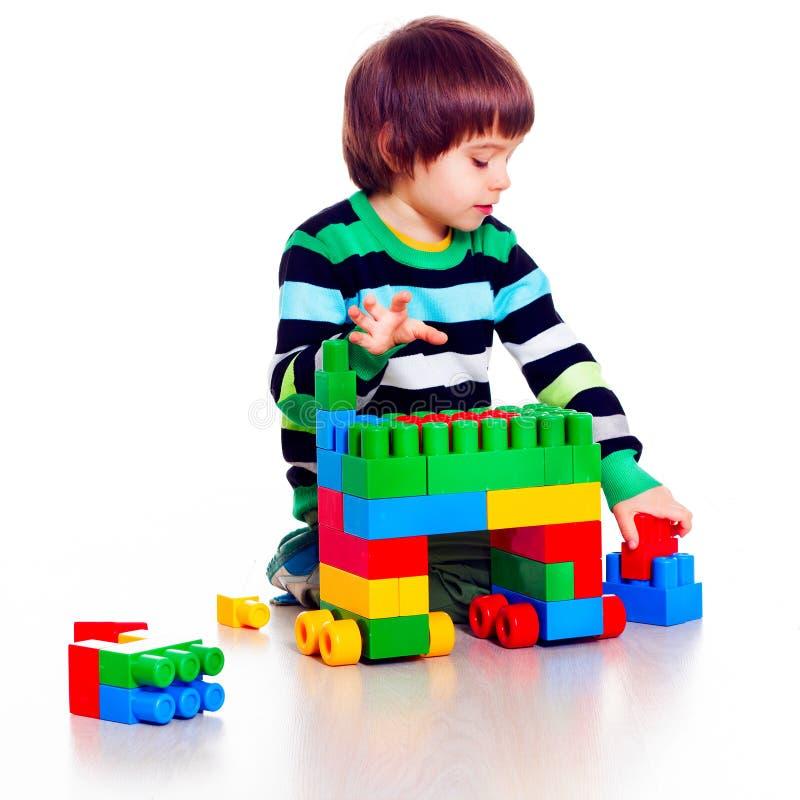 Kleiner hübscher Junge, der lego über weißem Hintergrund spielt lizenzfreie stockfotografie