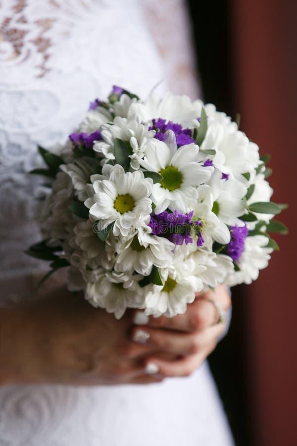 Kleiner Heiratsblumenstrauß in den Händen der Braut stockfotos