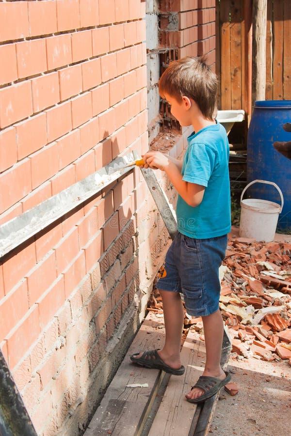 Kleiner Helfer, Junge bei der Arbeit stockbild