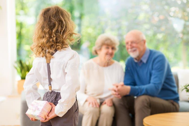 Kleiner Herr mit einem Geschenk für seine Großeltern lizenzfreie stockfotos