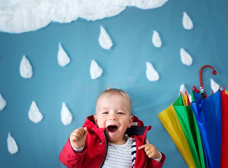Kleiner Junge auf blauem Hintergrund im Mantel mit Tropfen formt stockfotos