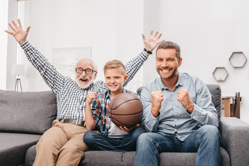 Kleiner Junge auf Couch mit dem Großvater und Vater, zujubelnd für ein Basketballspiel und halten a stockbild