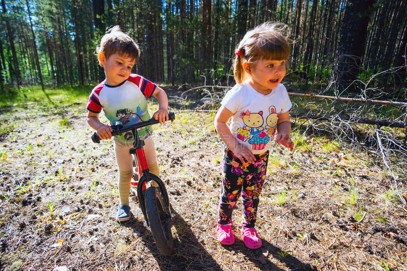 Kleiner Junge auf dem Fahrrad und Mädchen, die im Wald spielen stockfotografie