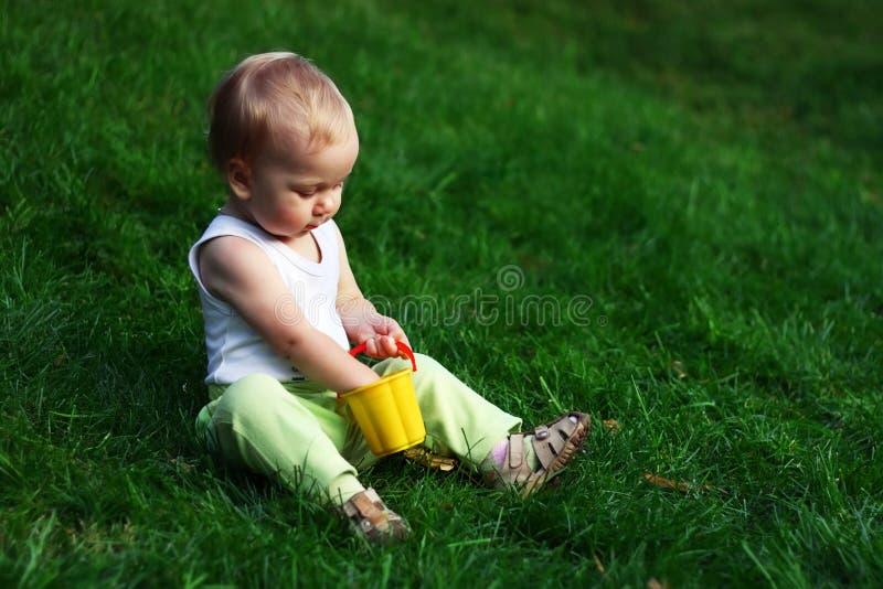 Kleiner Junge auf einem grünen Gras lizenzfreie stockfotos