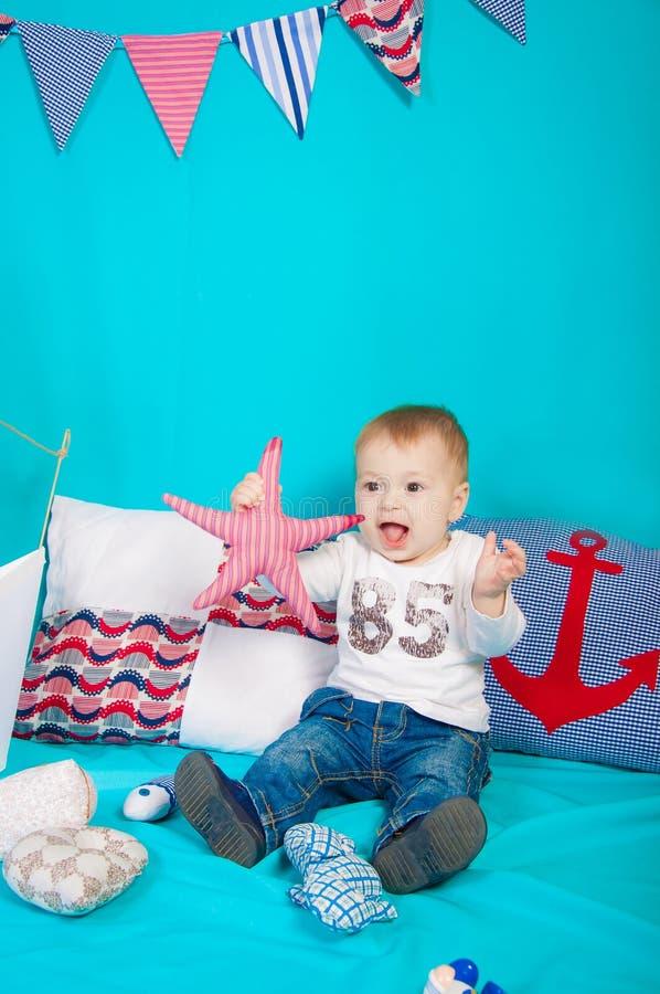 Kleiner Junge auf einem Hintergrund des Seedekors mit einem Spielzeug lizenzfreies stockfoto
