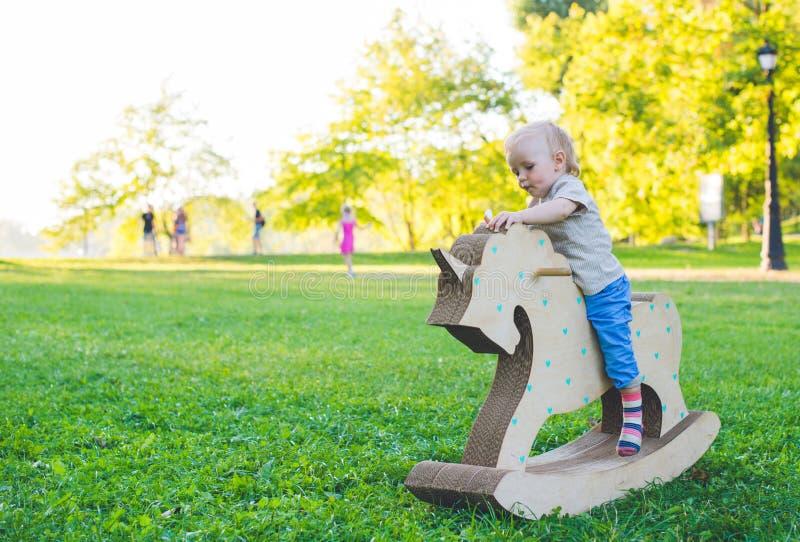 Kleiner Junge auf einem Spielzeugeinhorn Grasartiges Feld am Park Baum auf dem Gebiet Jungenlächeln und he& x27; s glücklich lizenzfreies stockfoto