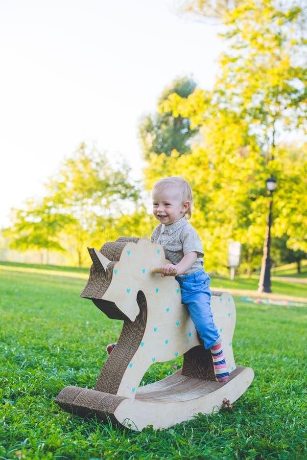 Kleiner Junge auf einem Spielzeugeinhorn Grasartiges Feld am Park Baum auf dem Gebiet Jungenlächeln und he& x27; s glücklich lizenzfreies stockbild