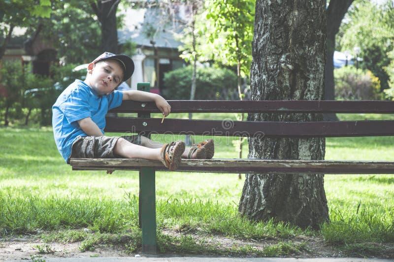 Kleiner Junge auf einer Bank lizenzfreie stockbilder