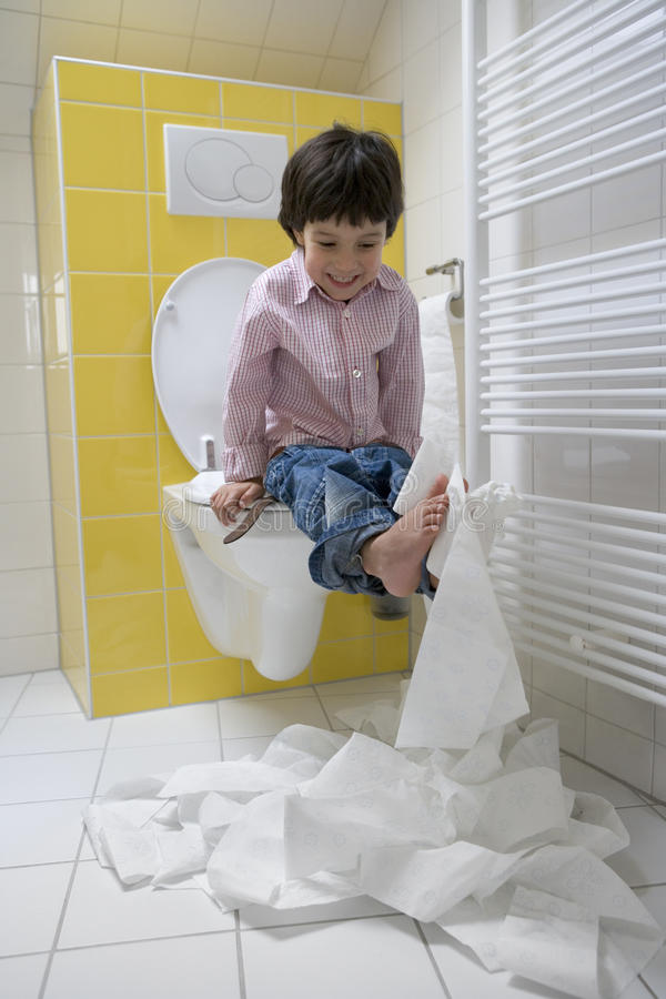 Kleiner Junge bildet eine Verwirrung mit Toilettenpapier in lizenzfreies stockfoto