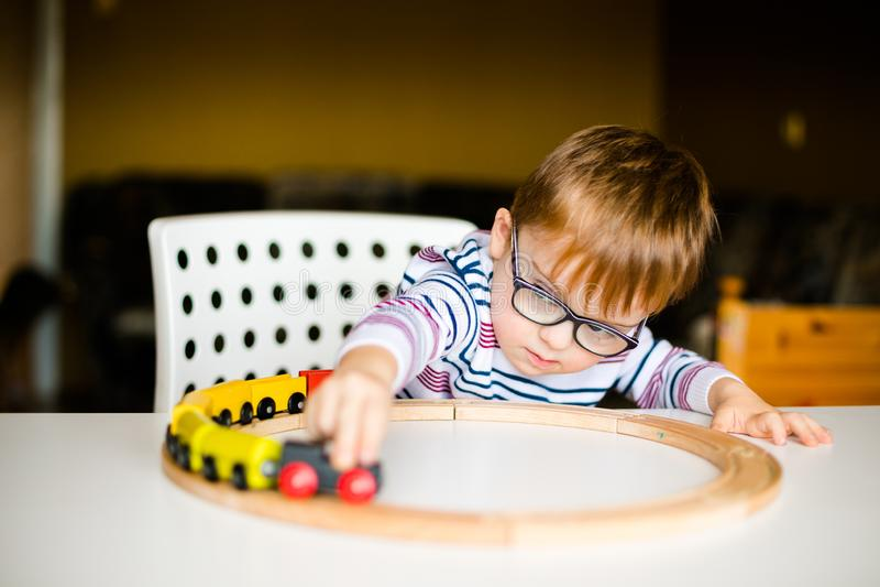 Kleiner Junge in den Gläsern mit der Syndromdämmerung, die mit hölzernen Eisenbahnen spielt stockfoto
