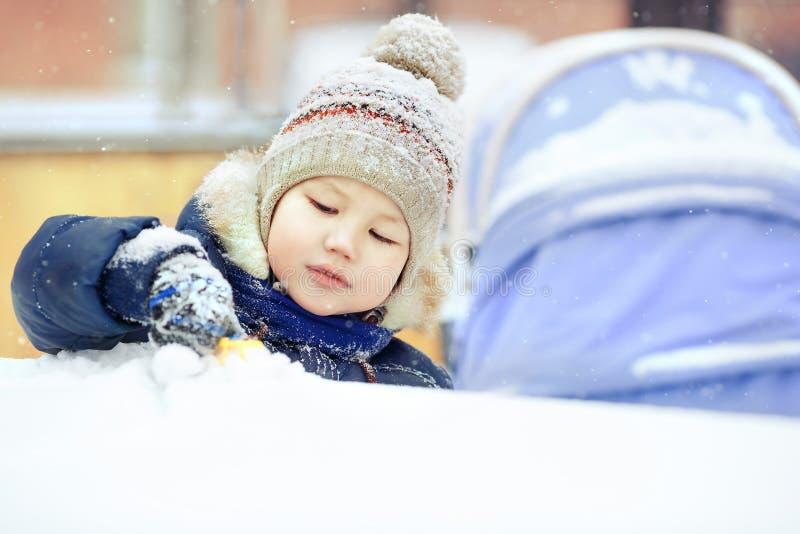 Kleiner Junge, der allein mit Spielzeug im Schnee, Abschluss oben spielt Draußen Winter stockfotografie