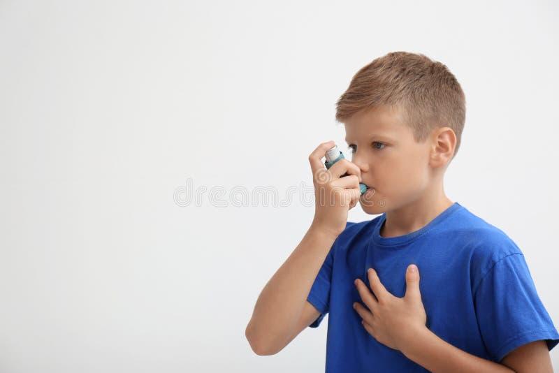 Kleiner Junge, der Asthmainhalator verwendet stockfotografie