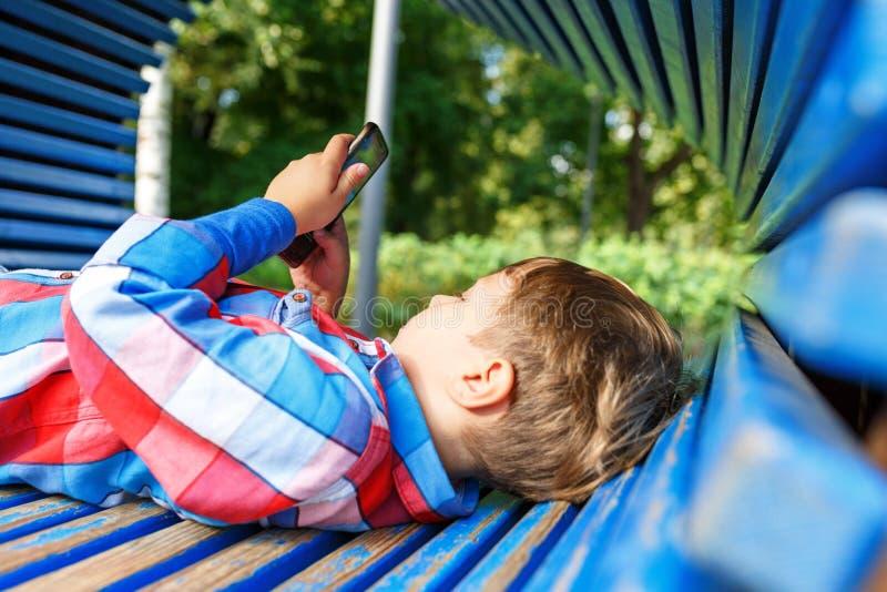 Kleiner Junge, der auf der Bank auf dem Spielplatz spielt am Handy liegt stockfoto
