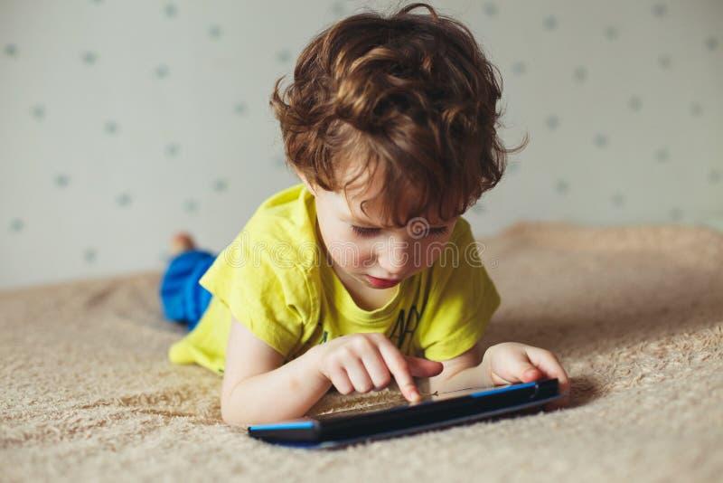Kleiner Junge, der auf Bett liegt und Tablette, unter Verwendung der modernen Technologie betrachtet lizenzfreies stockfoto