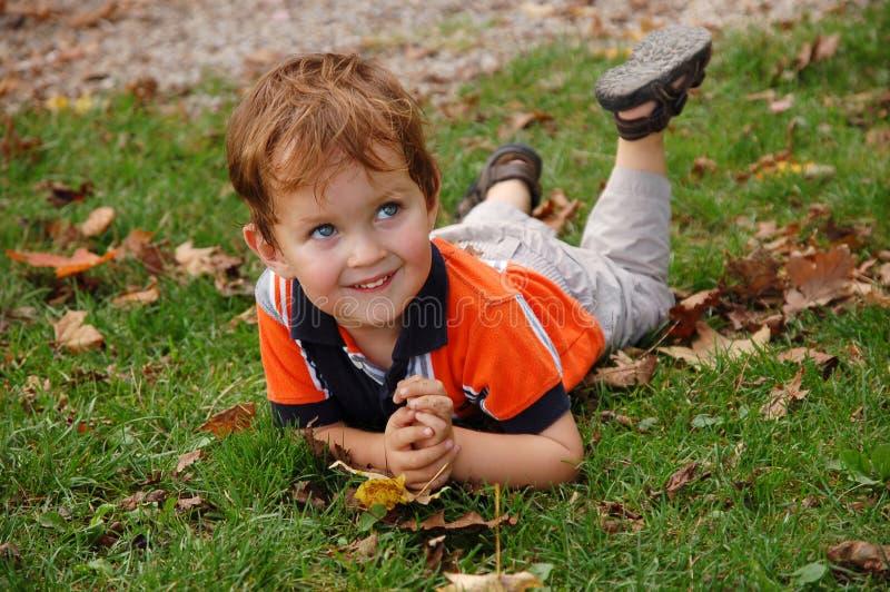 Kleiner Junge, der auf das Gras legt lizenzfreies stockbild
