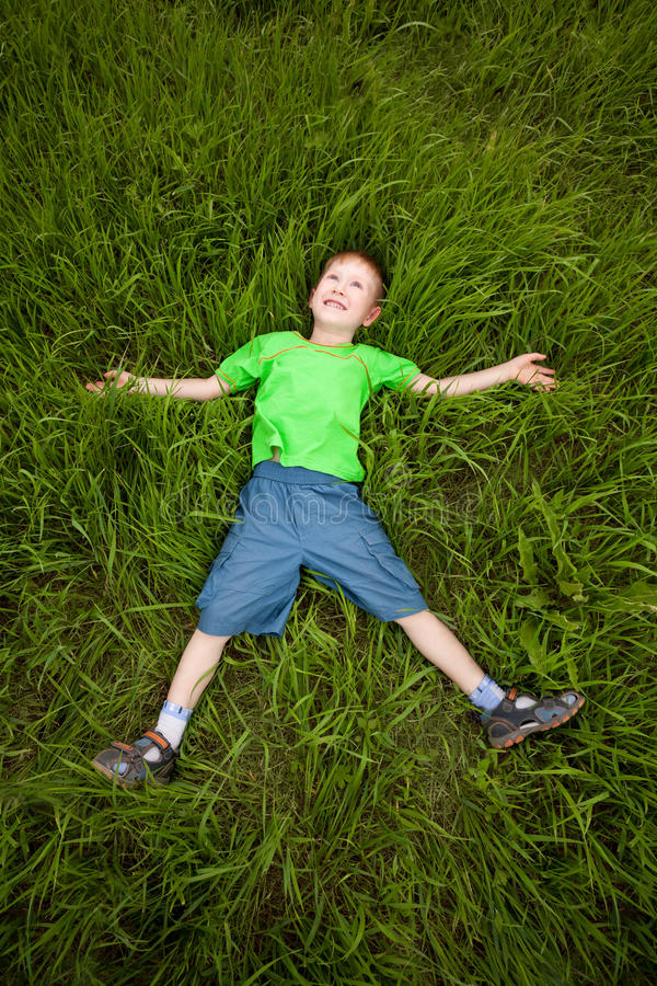 Kleiner Junge, der auf das Gras legt stockbilder