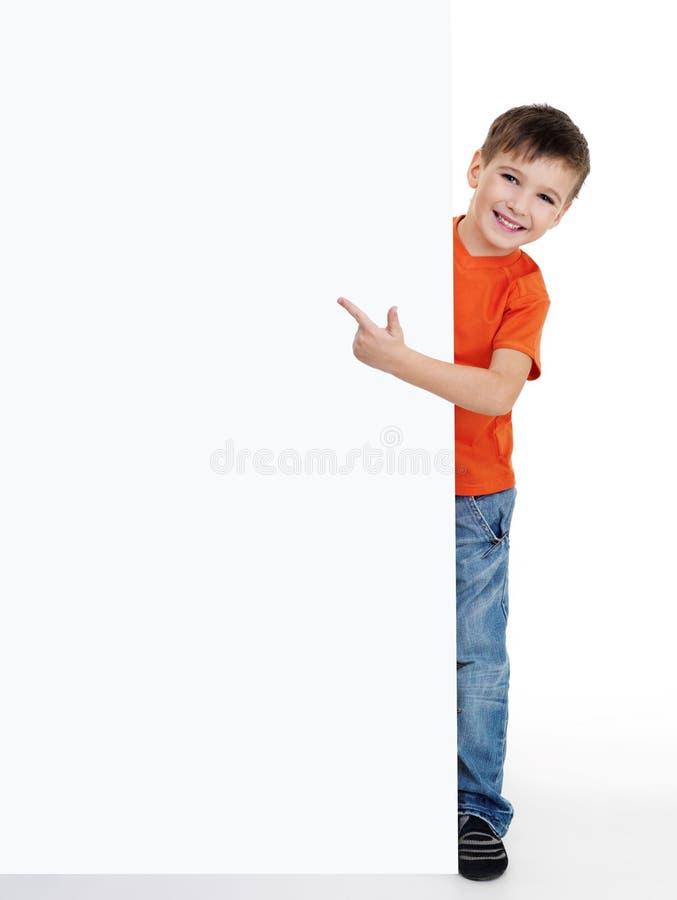 Kleiner Junge, der auf das unbelegte Plakat zeigt stockbilder