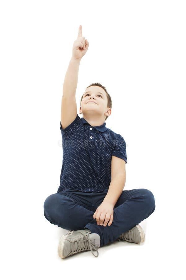 Kleiner Junge, der auf dem Boden zeigt leeren Kopienraum sitzt lizenzfreie stockfotografie