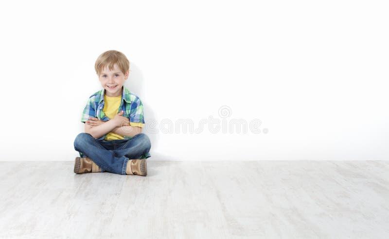 Kleiner Junge, der auf dem Fußboden sich lehnt an der Wand sitzt lizenzfreies stockbild