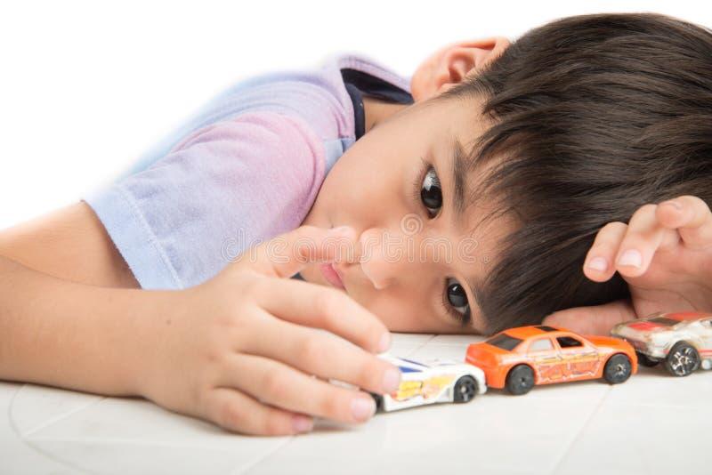 Kleiner Junge, der auf dem Tisch mit Autospielzeug allein spielt lizenzfreies stockbild