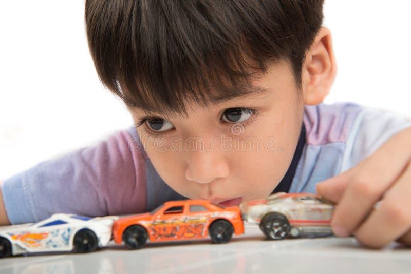 Kleiner Junge, der auf dem Tisch mit Autospielzeug allein spielt stockfotos