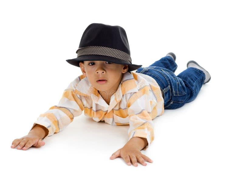 Kleiner Junge, der auf den Fußboden legt lizenzfreies stockfoto
