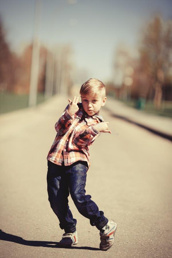 Kleiner Junge, der auf der Straße Gesicht verzieht stockbild