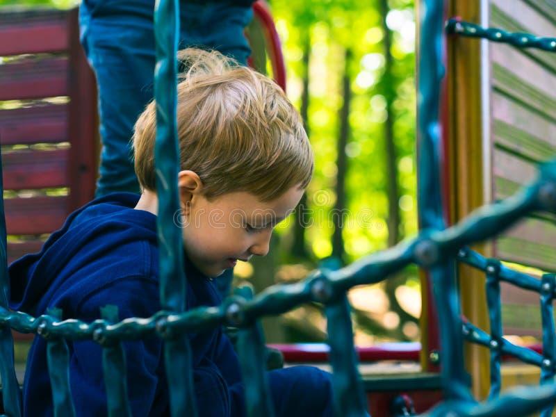 Kleiner Junge, der auf einem Spielplatz spielt aktivität stockfotografie