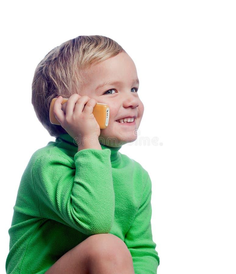 Kleiner Junge, der auf Handy spricht stockfotos