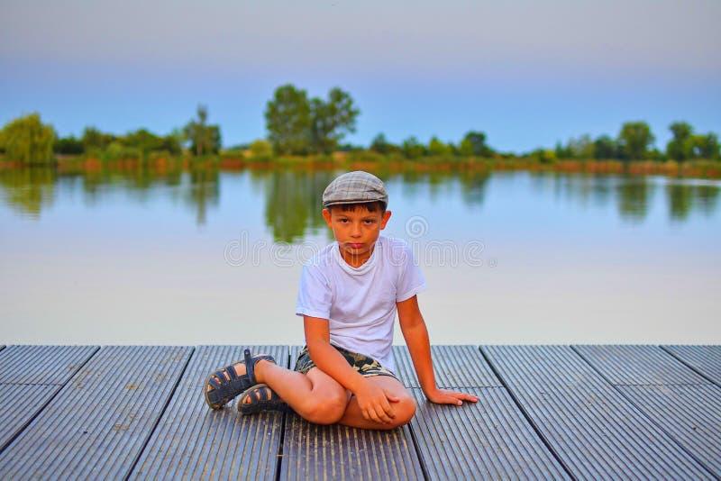 Kleiner Junge, der auf Pier sitzt Grundlegender Altersjunge, der auf einem hölzernen Pier sitzt Sommer und Kindheitskonzept Kind  lizenzfreie stockbilder