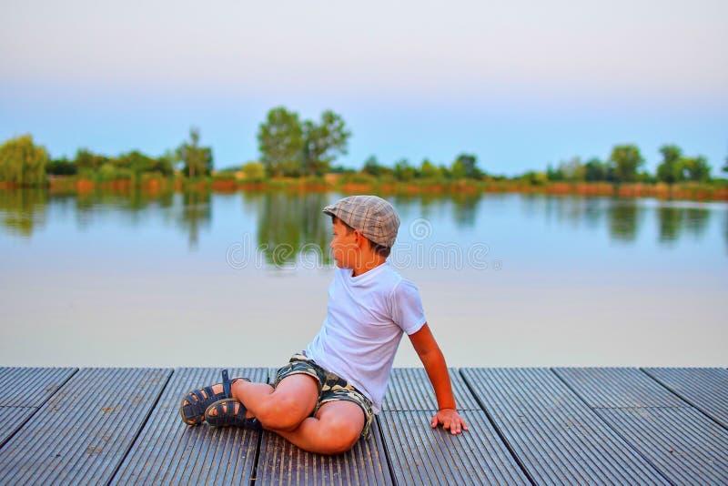 Kleiner Junge, der auf Pier sitzt Grundlegender Altersjunge, der auf einem hölzernen Pier sitzt Sommer und Kindheitskonzept Kind  stockfoto