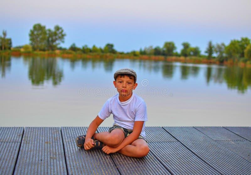 Kleiner Junge, der auf Pier sitzt Grundlegender Altersjunge, der auf einem hölzernen Pier sitzt Sommer und Kindheitskonzept Kind  lizenzfreie stockfotos
