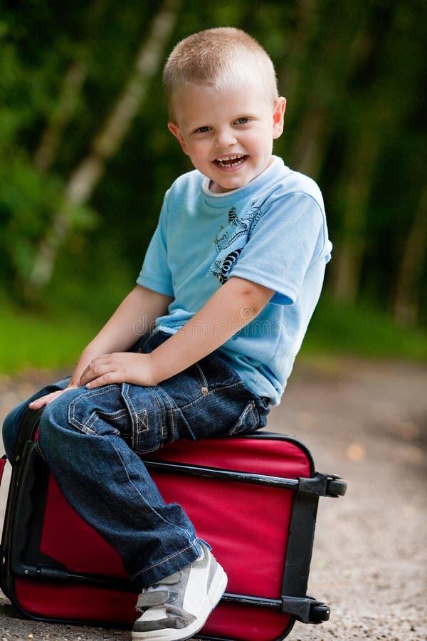Kleiner Junge, der auf seinem Koffer sitzt lizenzfreies stockbild