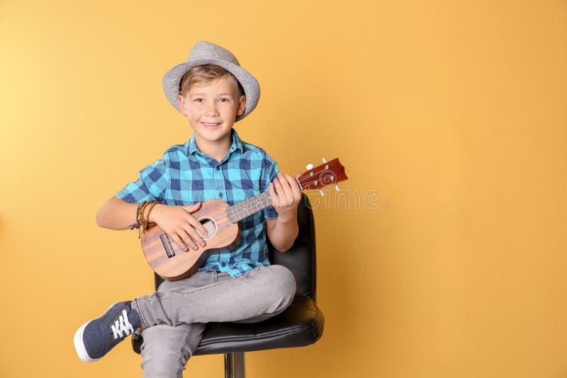 Kleiner Junge, der auf Stuhl sitzt und Gitarre gegen Farbhintergrund spielt stockfotografie