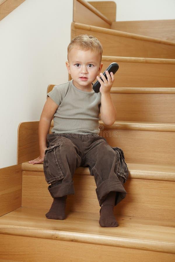 Kleiner Junge, der auf Treppen sitzt lizenzfreies stockfoto