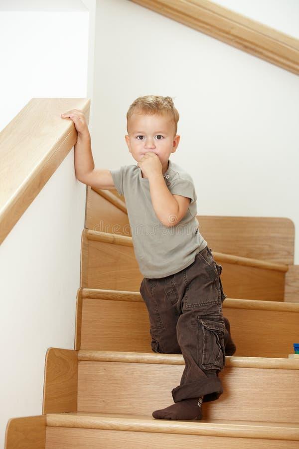 Kleiner Junge, der auf Treppen steht lizenzfreies stockbild