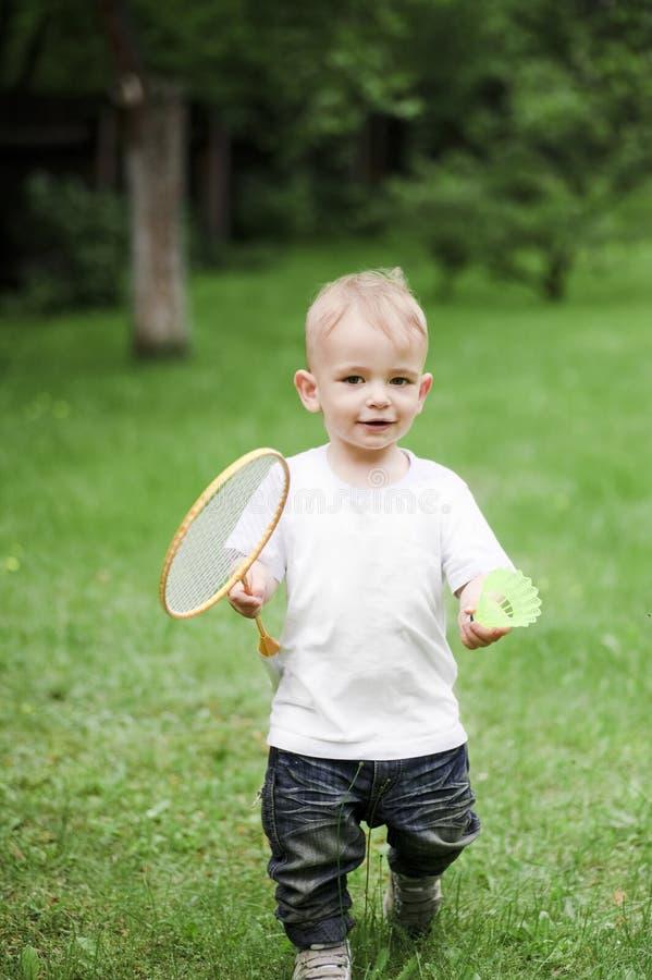 Kleiner Junge, der Badminton spielt stockbild