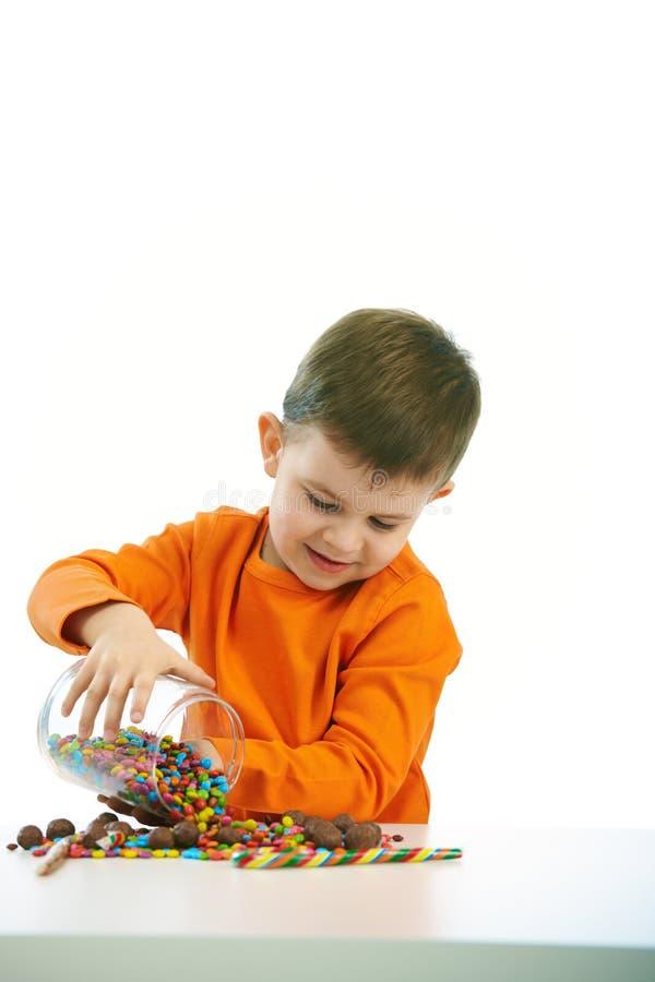 Kleiner Junge, der Bonbons isst volle Schüssel der Süßigkeit stockbilder