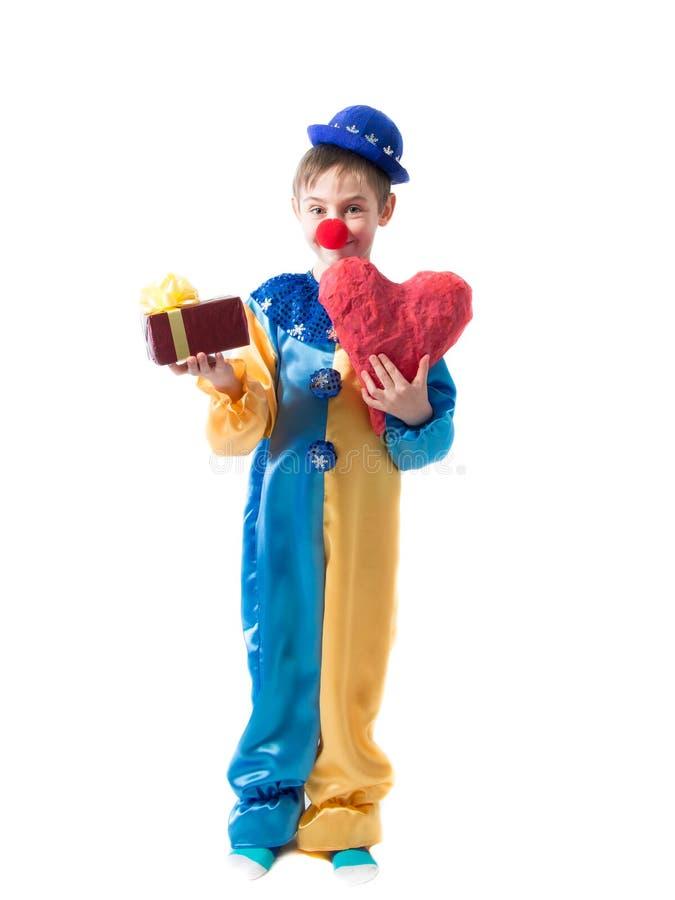 Kleiner Junge in der Clownklage, die einen Kasten mit einem Bogen in einer Hand und in einem großen roten Herzen in der anderen H lizenzfreies stockbild