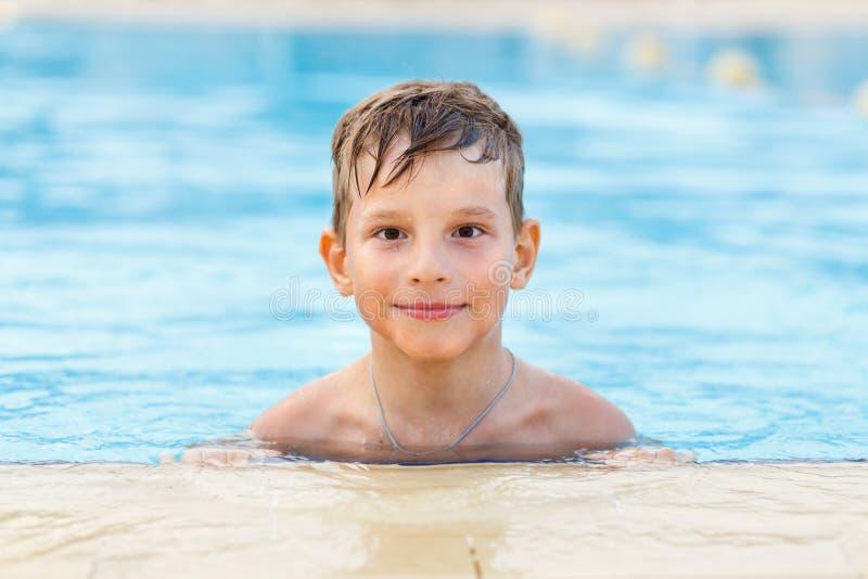 Kleiner Junge, der das Schwimmen im Pool genießt stockbild