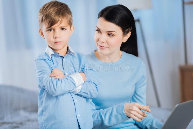 Kleiner Junge, der das Umkippen gescholten wird von der Mutter schaut lizenzfreies stockbild