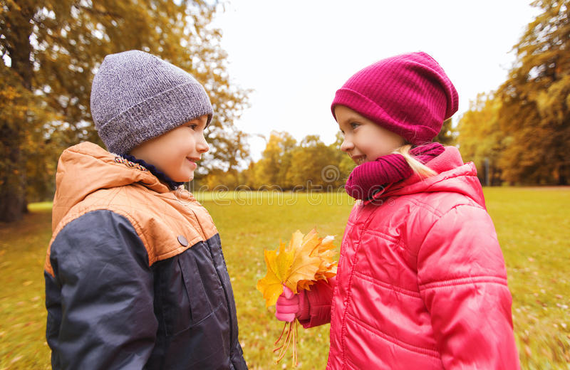 Kleiner Junge, der dem Mädchen Herbstahornblätter gibt lizenzfreie stockbilder