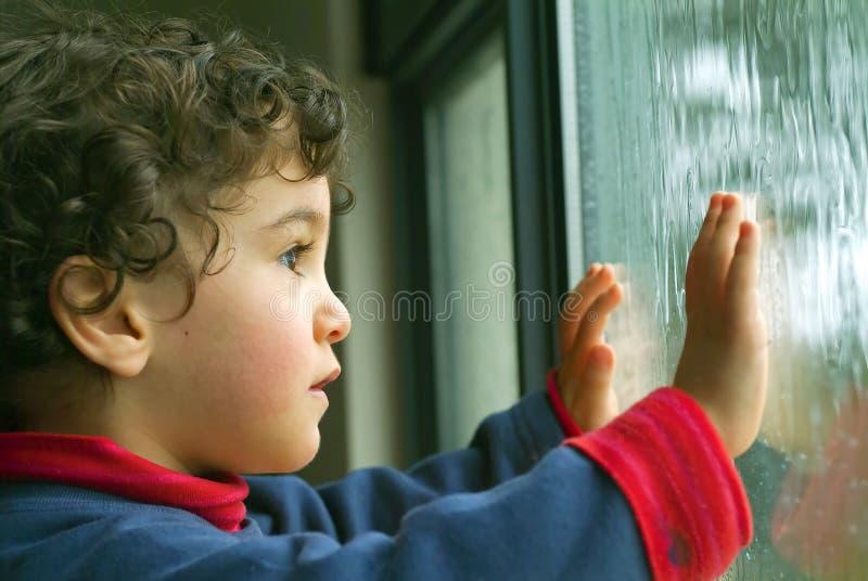 Kleiner Junge, der den Regen überwacht stockfotografie