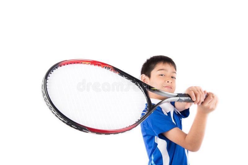 Kleiner Junge, der in der Hand Tennisschläger und -Tennisball spielt stockbild