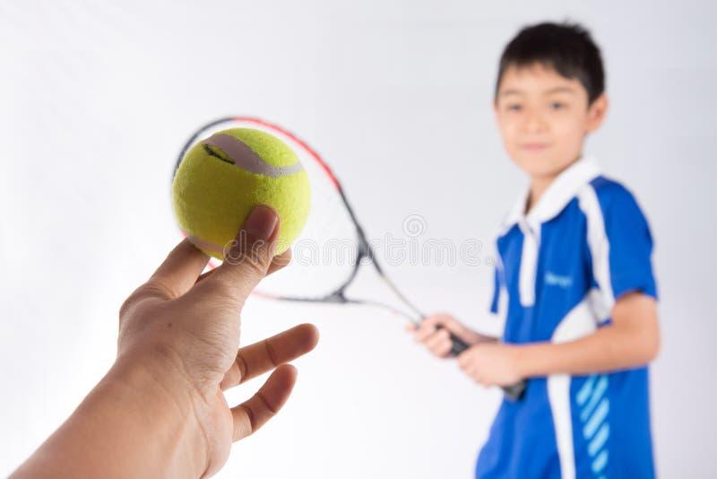 Kleiner Junge, der in der Hand Tennisschläger und -Tennisball spielt lizenzfreies stockbild
